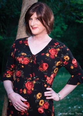Allison leans against a tree