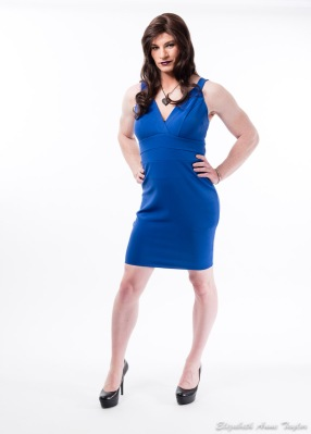 Desi stands with hands on hips wearing a blue dress
