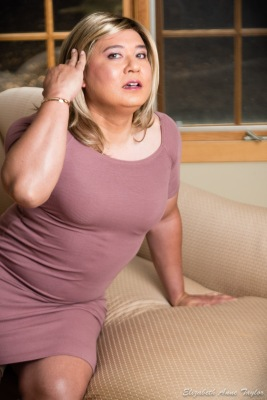 Gina wears a mauve dress and tucks her hair behind her ear while seated