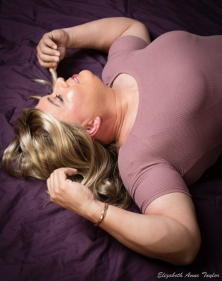 Upper body shot of Gina while laying on a purple comforter