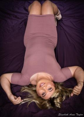 Full length shot of Gina lying on purple blanket