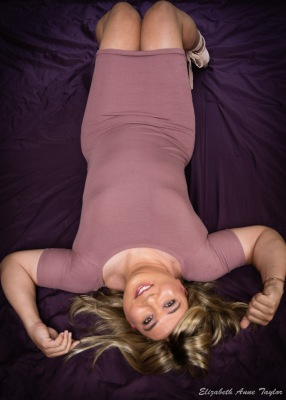 Full length shot of Gina lying on purple blanket