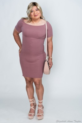 Gina stands in mauve dress matched with pale pink purse and beige wedge sandals