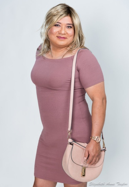 Gina stands in mauve dress and pale pink purse