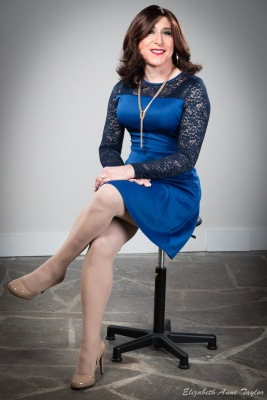 Stacie Stevens sits in blue dress with leg crossed at knee