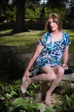 Allison sits on a garden bench in a purple and blue dress. She slips her heel on. Grass and trees are in the background.