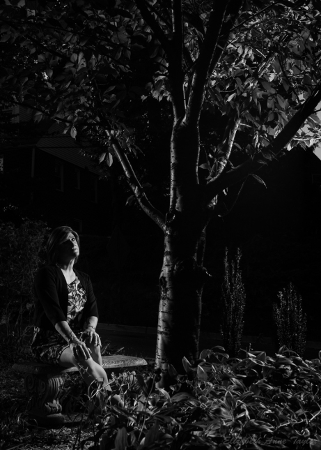 Black and white image of Allison sitting on a garden bench under a cherry tree. She and the tree are illuminated from opposite sides.