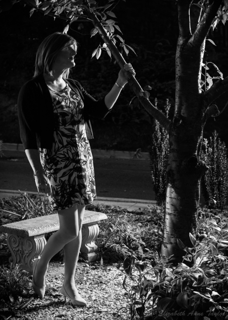 In this black and white photo, Allison grabs onto a branch of the cherry tree.