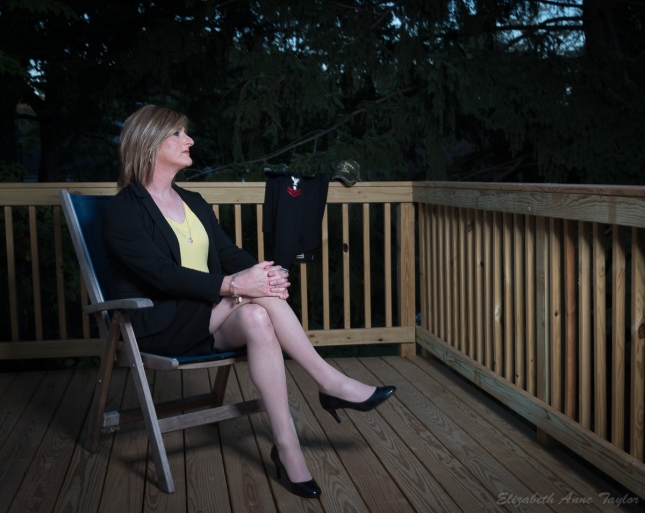 Allison wears a black black and skirt with a yellow top and black heels. She sits in a patio chair with her Navy service dress jumper in the background on the deck railing.