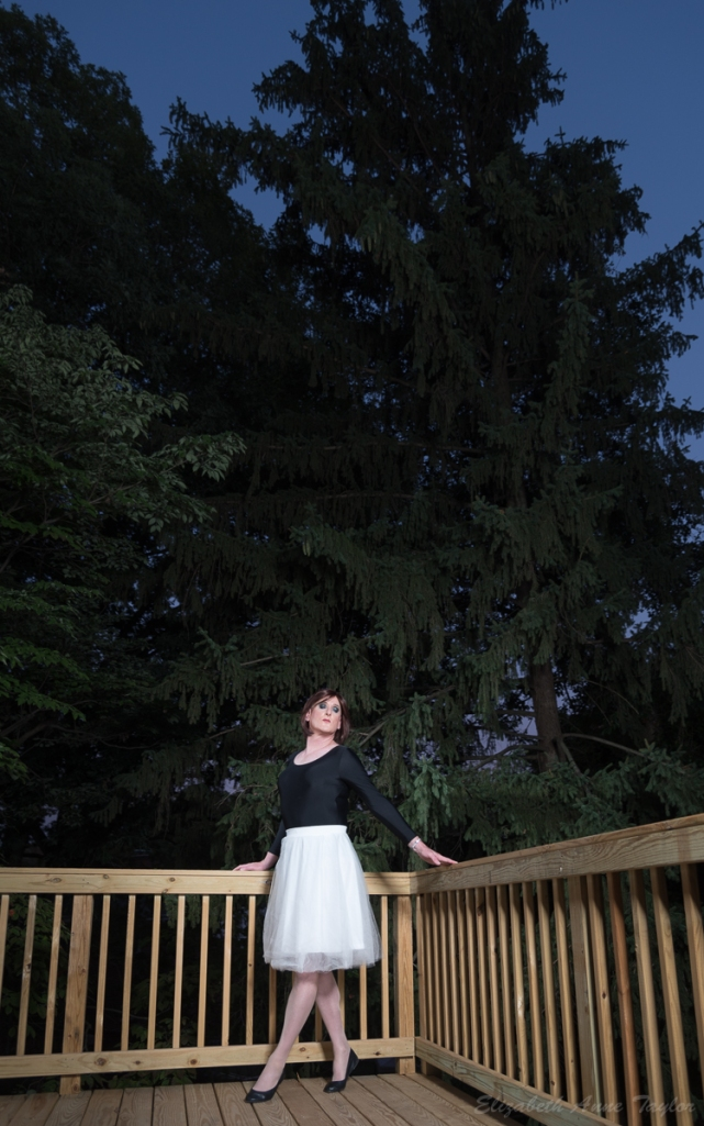 Allison is dressed as a ballerina in a black leotard and white, full skirt. She wears black ballet shoes. She is on a corner of a wood deck with a large pine tree and the purple-blue sky of twilight behind her.