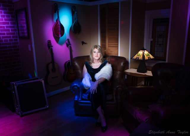 Allison wears longer, blond hair with a blue, velvet dress with a white faux fur wrap. She is seated in a leather, overstuffed chair with a lamp, club lights, and musical instruments in the background.