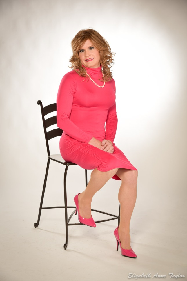 Cari sits on a barstool in a pink dress with pearls.