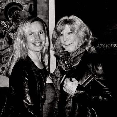 Two women wear leather jackets and smile