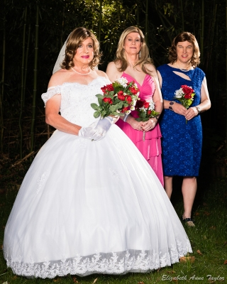 Bride in white stands next to two bridesmaids