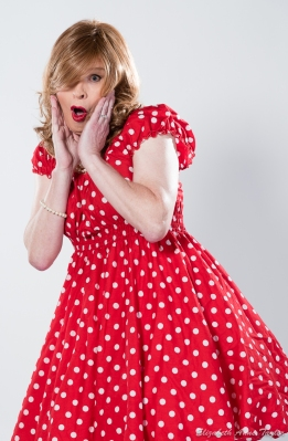 Pin-up girl looks surprised. She wears a red and white polka dot dress with a petticoat.