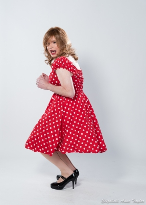 Pin-up girl in red and white polka dot dress and black mary jane shoes shimmies to music