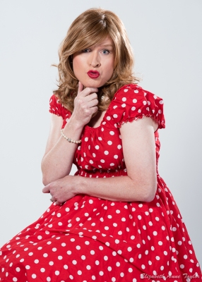 Tiffany sits in a red and white polka dot dress with hand under her chin